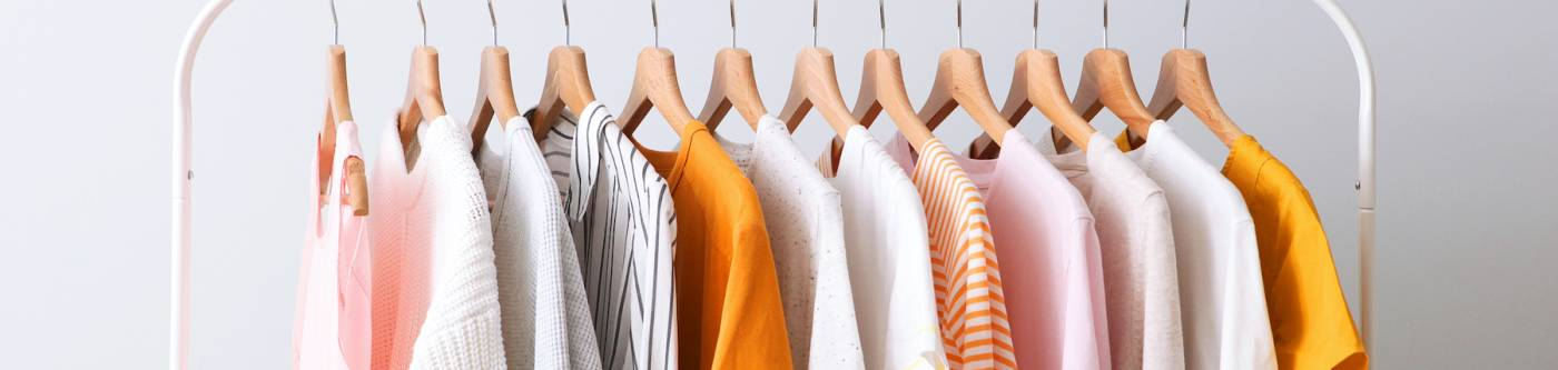 rack of clothing in orange, pick, and white colors